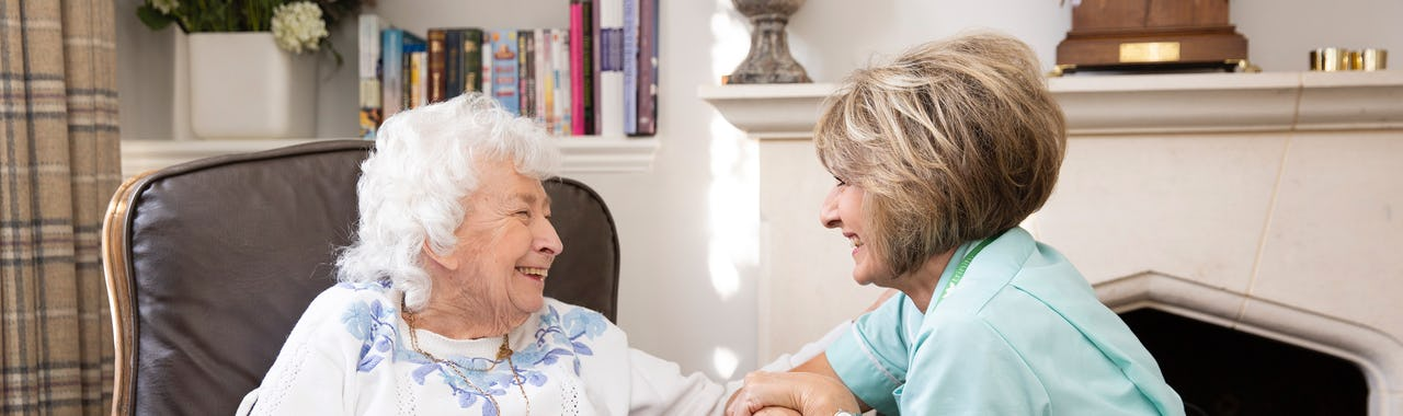Elderly Lady Sitting with her Carer, both laughing together