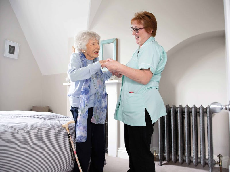 A Dementia patient being helped up by her nurse