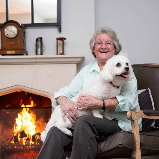 A woman enjoying live-in care with her white dog sitting on her lap by an open fire