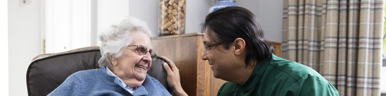 Elderly lady sat in a chair talking to her carer