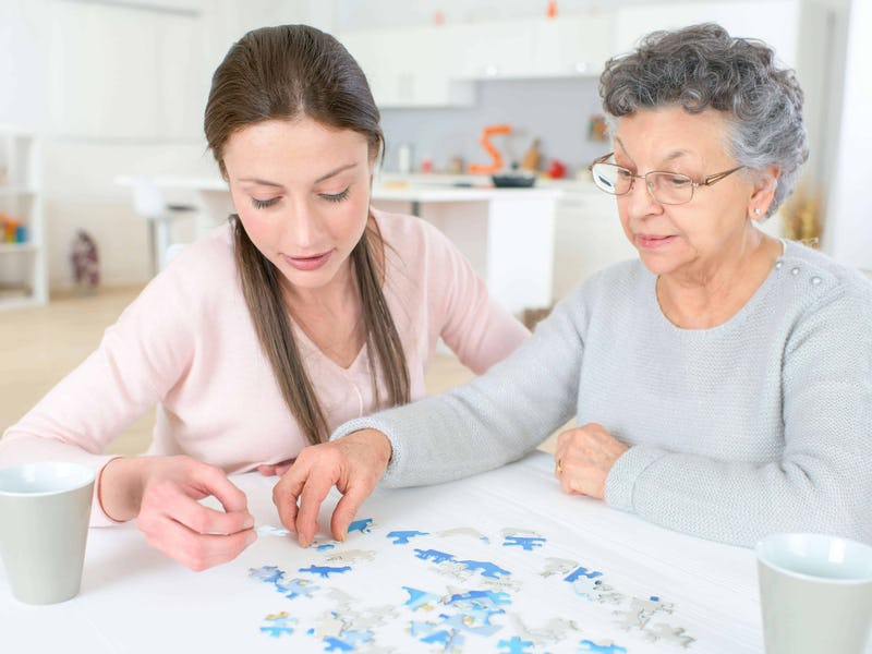 Carer supporting a lady with dementia complete a puzzle