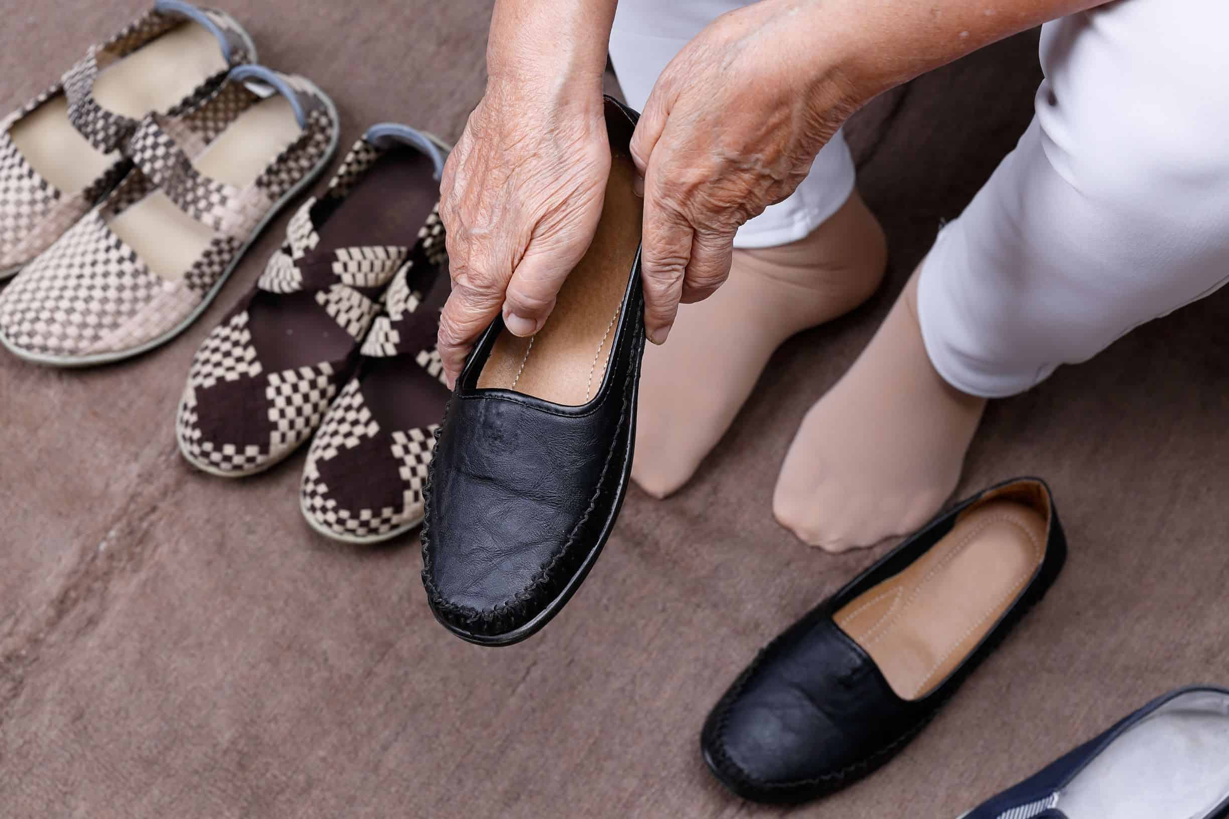 Elderly putting on supportive shoes