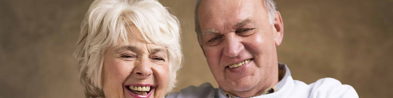 Elderly couple sat on the sofa together using a tablet and enjoying themselves