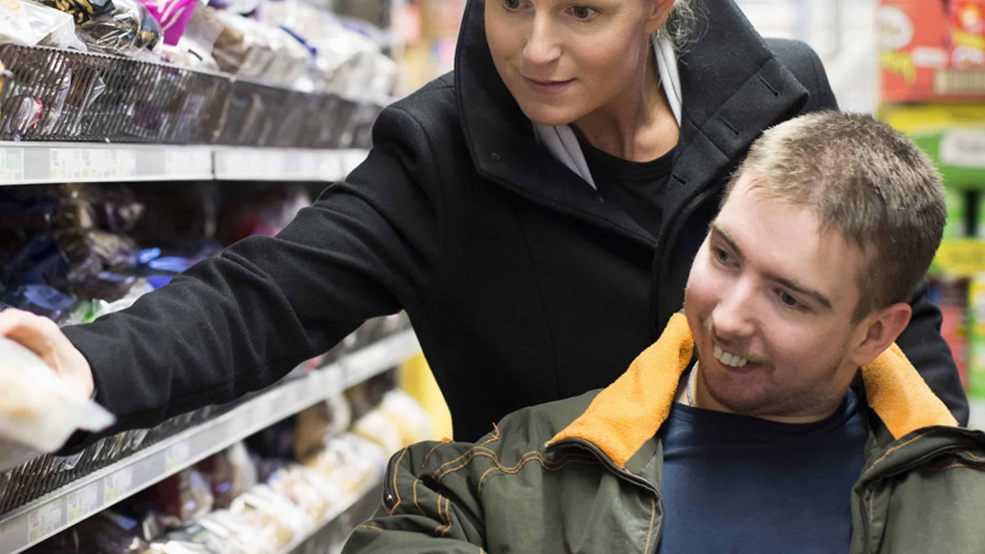 Carer supporting a young male client shopping