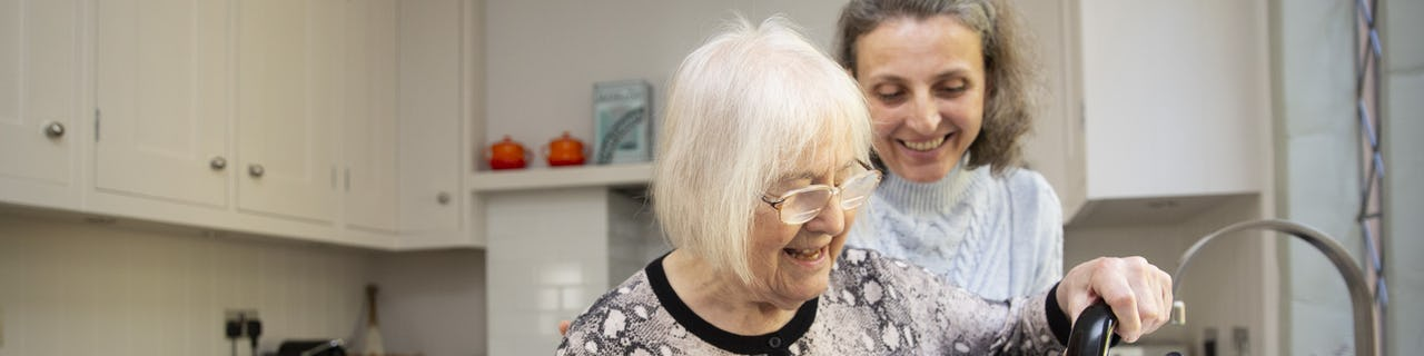 Elderly Lady with Kettle being supported by her Carer