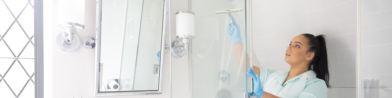 Carer cleaning a shower in a clients home