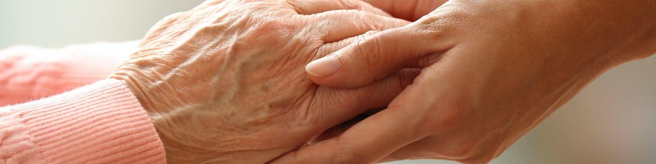 Young hands holding elderly hands