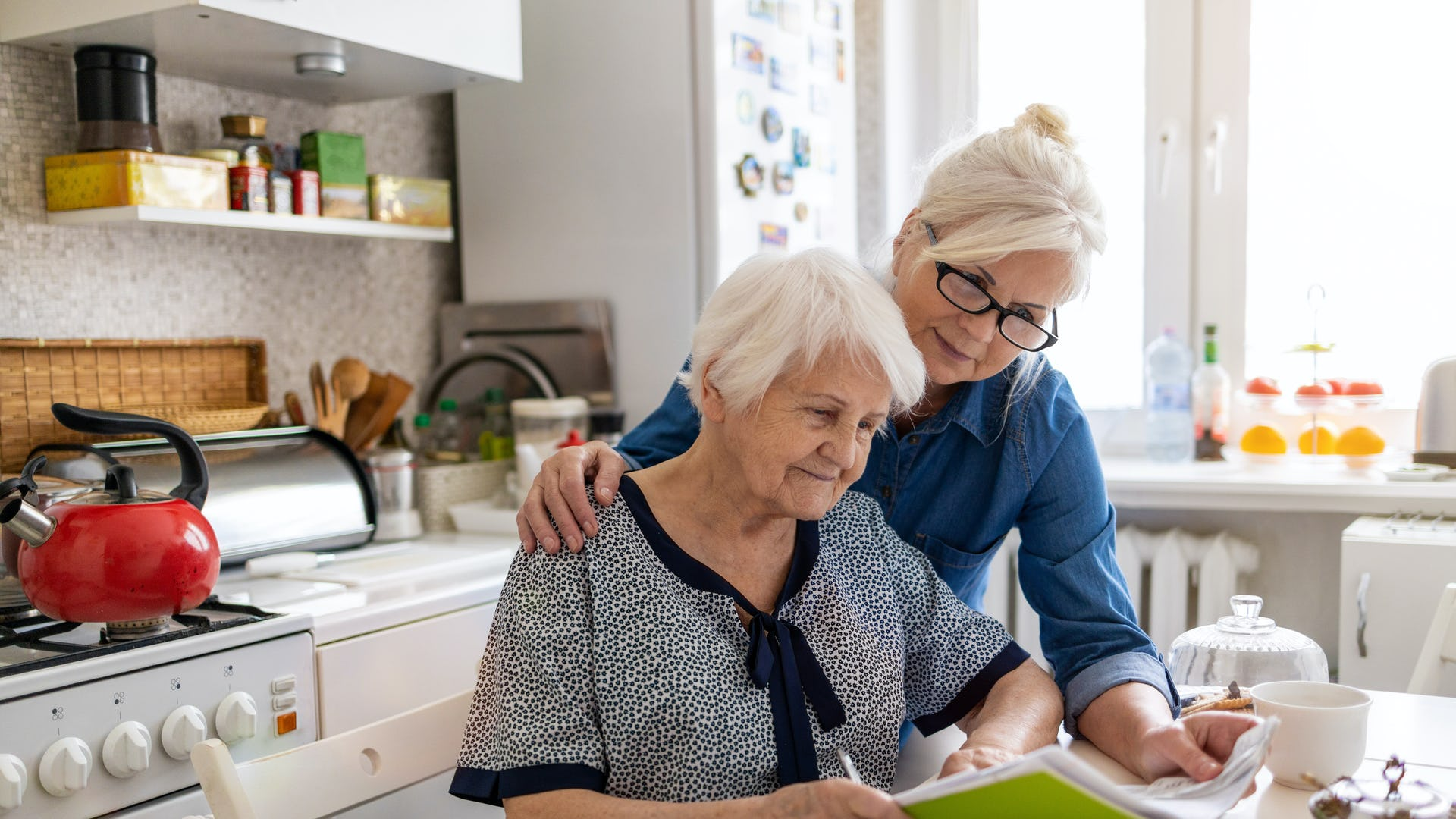Carer helping elderly lady complete her expenses tracking