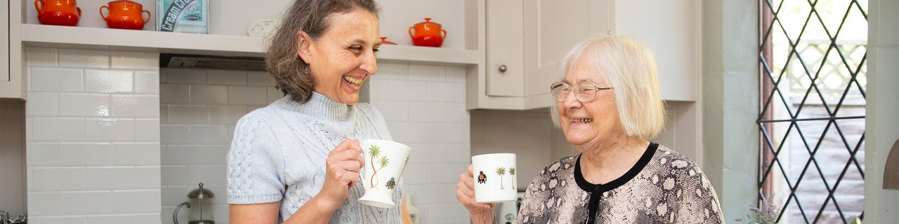 Elderly lady enjoying a cup of coffee with her carer