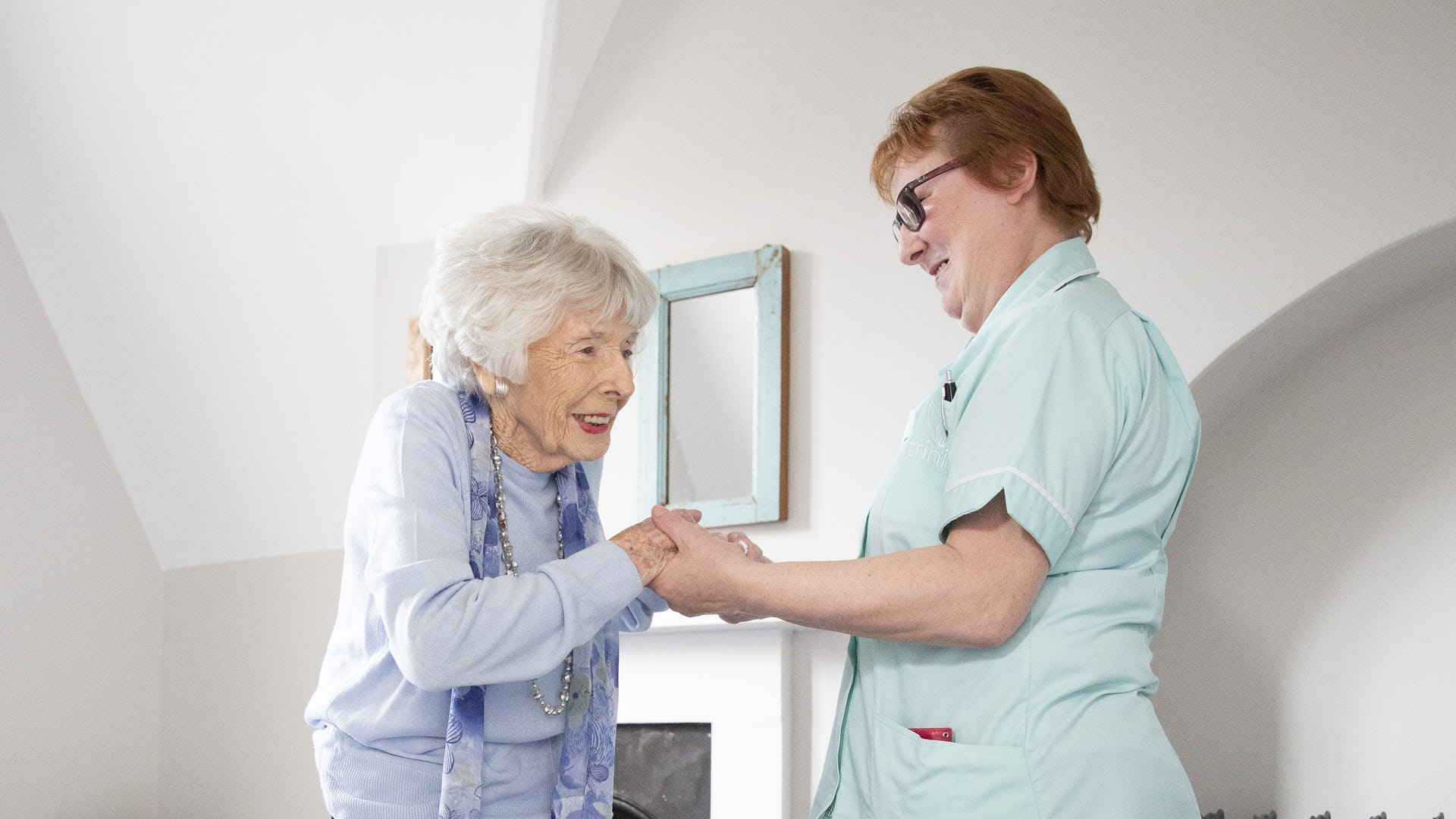 Carer supporting elderly client to stand Up