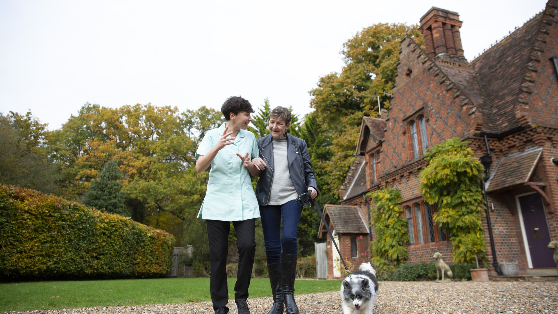 Carer and Client outside walking a dog