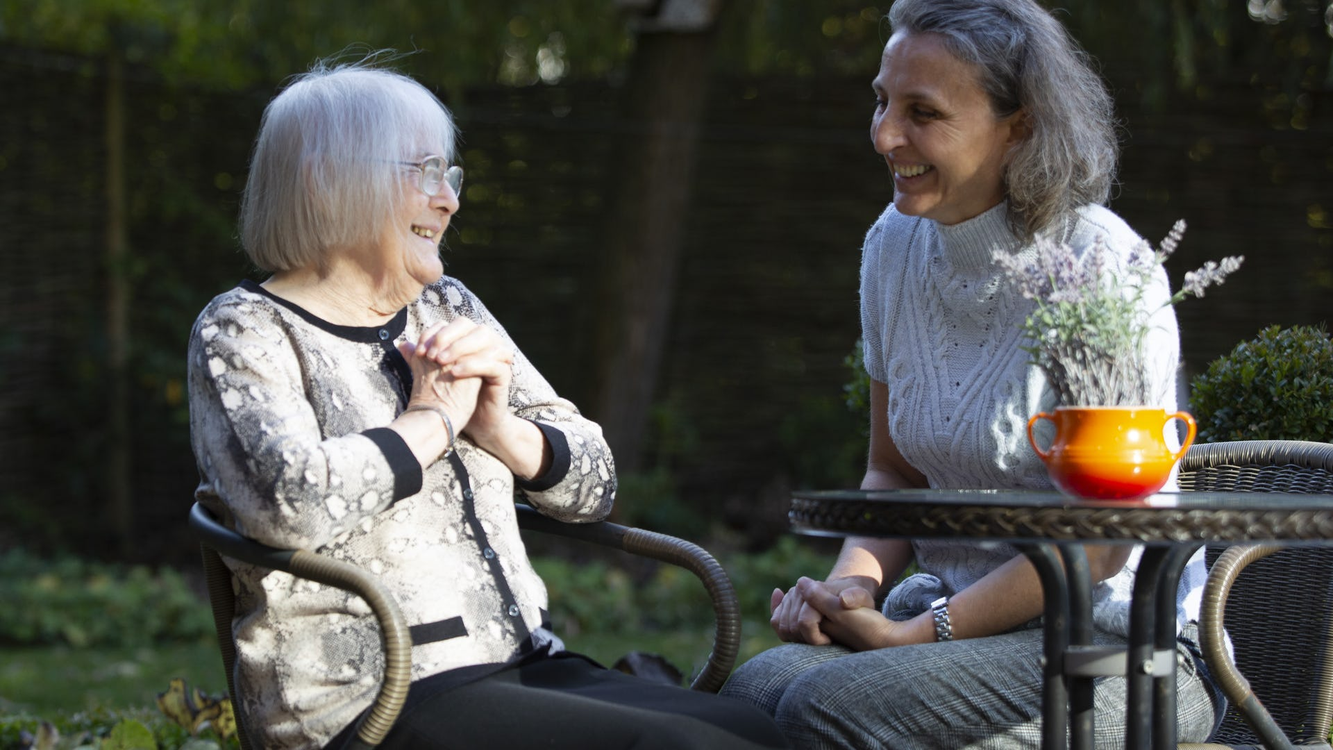 Carer and elderly lady sitting in the garden
