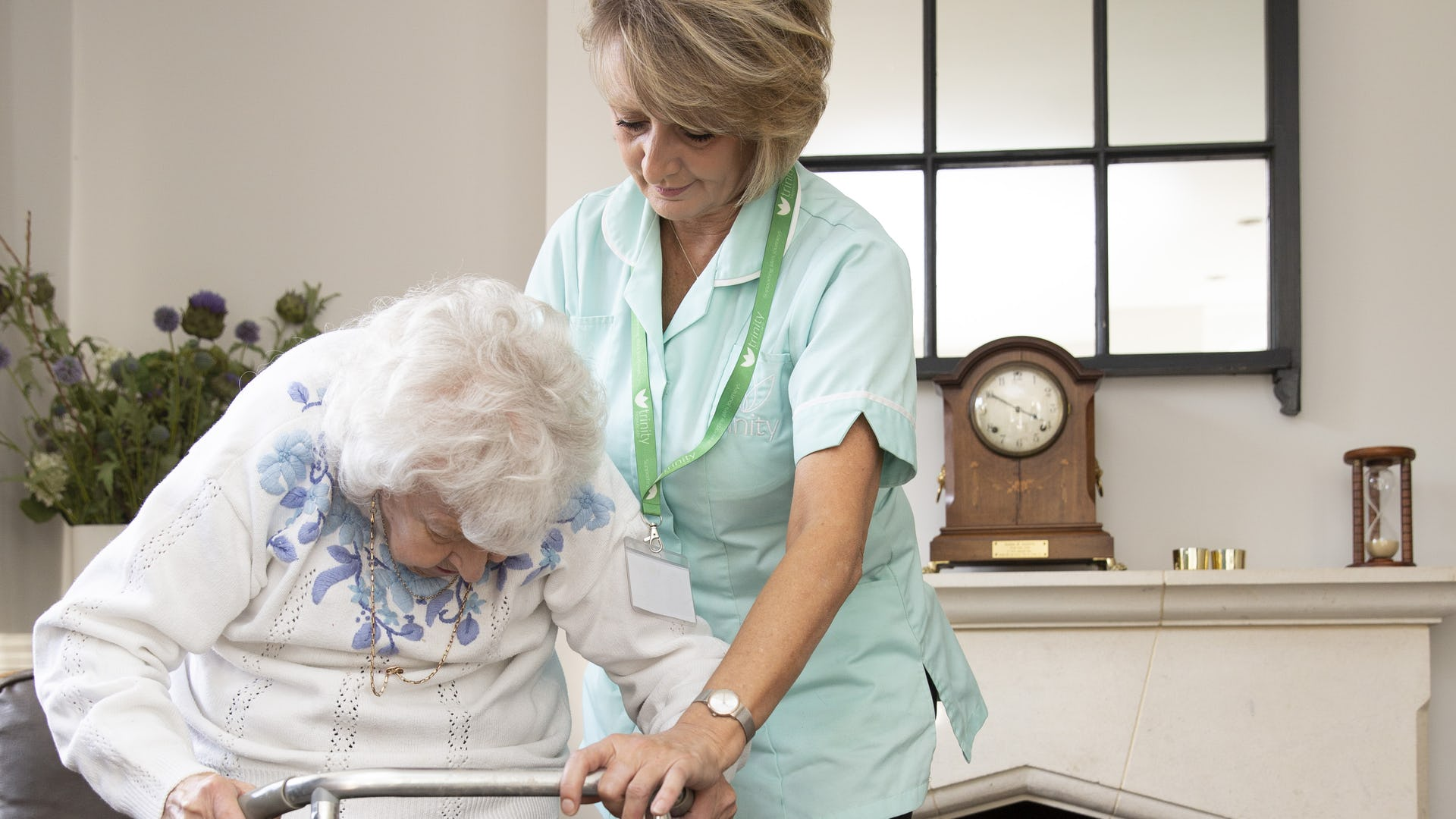 Carer supporting while elderly person is using a walking frame