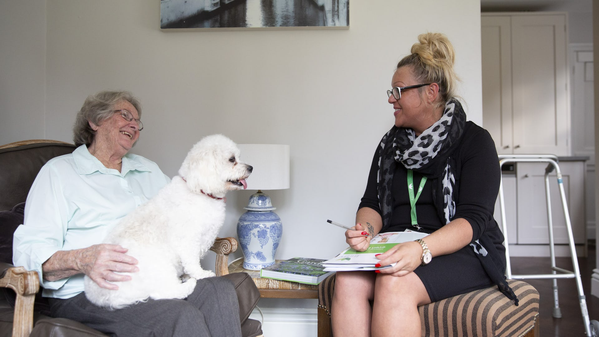 Elderly Lady sat in a chair with her per dog on her lap talking to a care manager