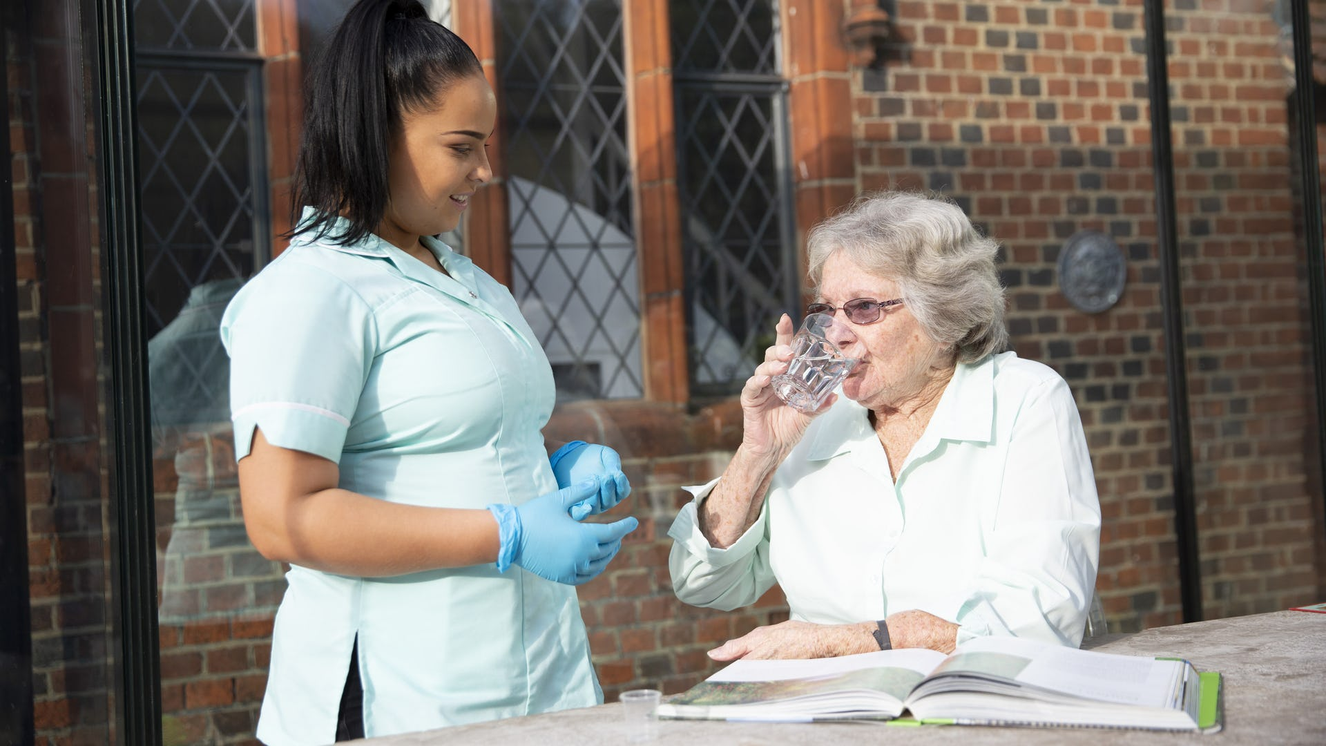 Elderly lady supported taking her medication given by a trained carer