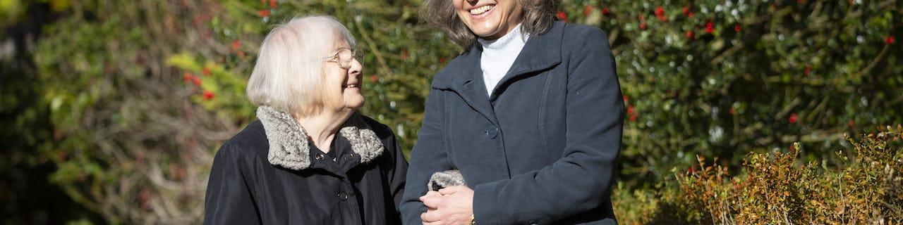 Two elderly ladies outside walking arm in arm