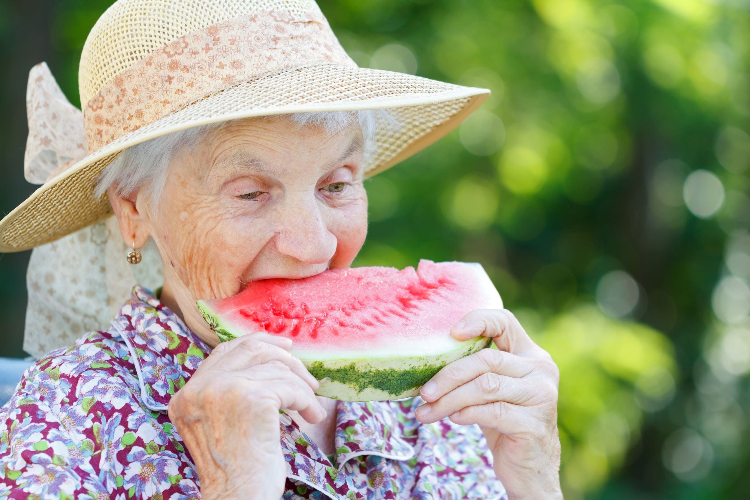Elderly woman eating a watermelon in the summer