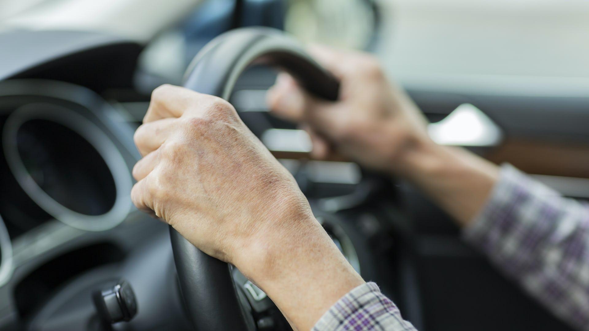 Elderly hands on a steering wheel